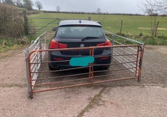 Un fermier a construit un gard de metal în jurul unui BMW, supărat că șoferul a parcat în fața porților de acces