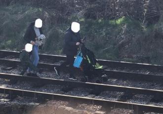 Doi tineri iresponsabili, surprinși plimbându-și copilul pe calea ferată, în Anglia