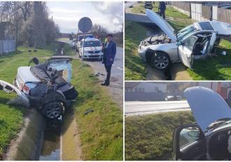 BMW rupt în două pe un drum din Gorj, jumătate din maşină a fost aruncată pe partea opusă a şoselei